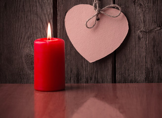 red candle and paper heart on wooden background
