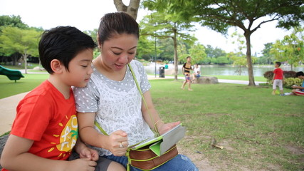 Asian mom with her children playing tablet  in the park .