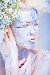 Portrait of woman with unusual bleu paint make-up with flowers