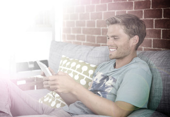 Cheerful young man using tablet in sofa