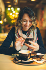woman with smart phone in coffee shop