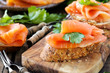 Smoked salmon canape with parsley leaf on rustic wood