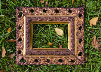 antigue  picture frame on autumn grass with yellow leaves