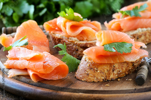 Fotobehang Snack Smoked salmon free canape parsley leaf on wood