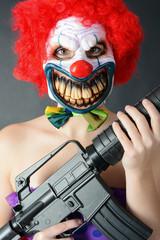 Horror-Clown hält Maschinengewehr