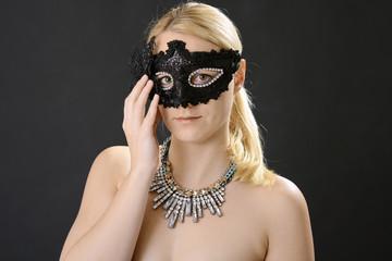 Frau trägt Maske und Collier zu Maskenball