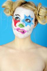 Clown mit bunter Schminke schaut verlegen