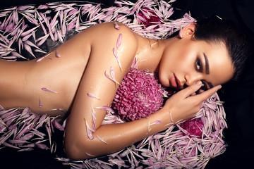 beautiful woman lying in petals of chrysanthemum in bathtub