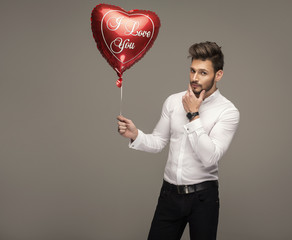 Handsome man with balloon heart thinking