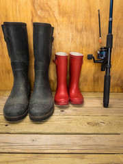 mans and boys rubber boots with  fishing rod