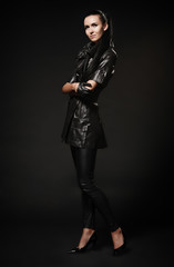 girl in a leather black coat, pants and shoes, standing on a bla
