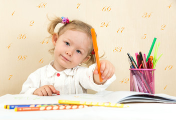 Cute child girl drawing  in preschool at table