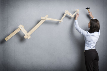 Young businesswoman building pointing up chart.