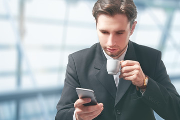 businessman with mobile phone and coffee cup