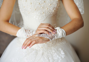 hands of a bride with a manicure and gloves