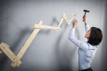 Confident woman building positive trend graph with hammer in han