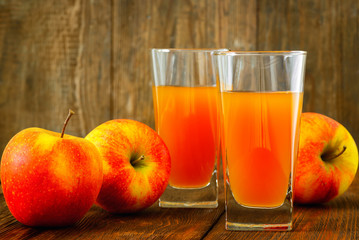 Two glasses of apple juice and apples on wooden background