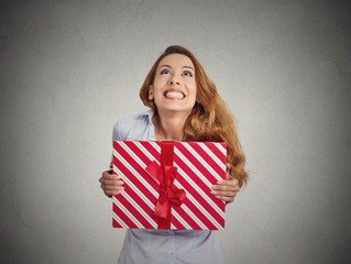 Gift box in hands of young happy woman on grey background