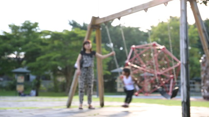 Child rides a swing in Thailand park with your mom .