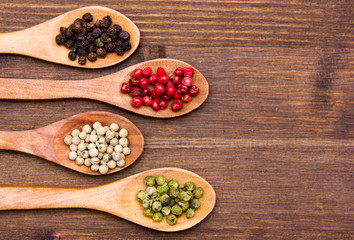 Wooden spoons with mixed peppers on one side on wooden table