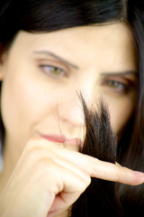 Woman looking ends of hair to see if it is ruined