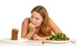 Leinwandbild Motiv woman deciding whether to eat healthy food or sweet cookies