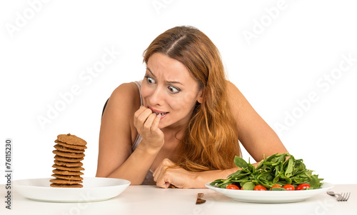 woman deciding whether to eat healthy food or sweet cookies - 76115230