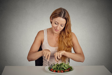 young woman eating green salad isolated grey wall background