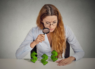 Businesswoman looking through magnifying glass at dollar signs