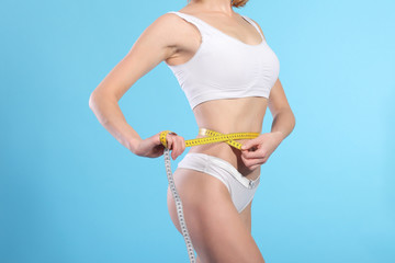 woman with measure tape over white