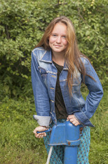 Young long haired girl in denim jacket outdoors in the village.