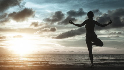 Silhouette of young woman meditating on the ocean beach.