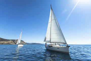 Yachts. Sailing in the wind through the waves at the Sea.