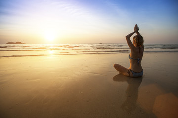 Girl sit at the seaside and meditating in yoga pose.