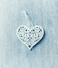 Vintage heart shaped decoration on a painted wooden surface