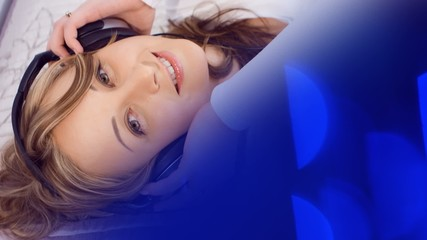 Happy young woman listening to music, blue background
