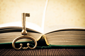 Old metal key and open book