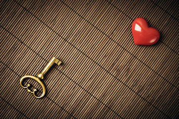Old metal key and red heart on the brown mat