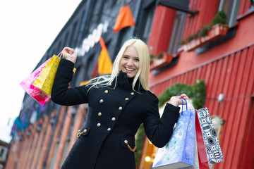 Smiling pretty blond girl with shopping bags
