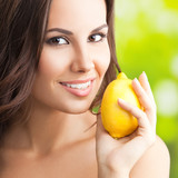Smiling woman with lemon, outdoors