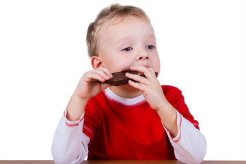 Small boy eating whole bar of chocolate