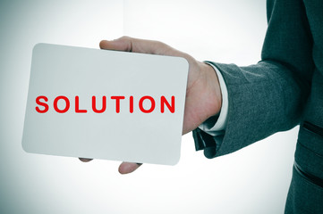 businessman showing a signboard with the word solution