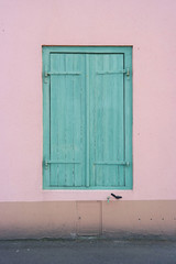 Pastel Window with green shutters, set in a pink plastered wall