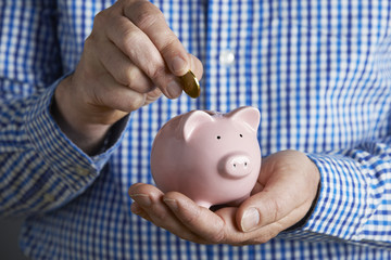 Man Putting Coin Into Piggy Bank
