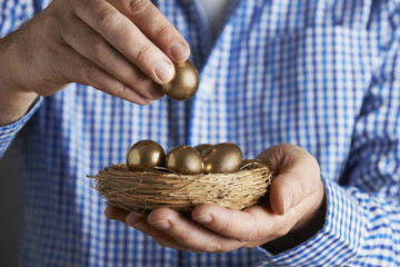 Man Holding Nest Full Of Golden Eggs