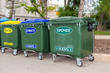 Green dumpsters on a city street with inscription on russian: ""