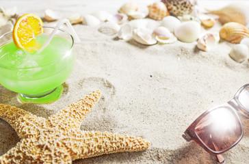 Cocktail am Strand mit Muscheln und Seestern