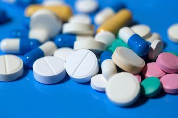 pills. White medical pills on blue background