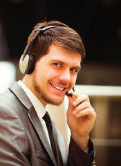 young man working at callcenter, using headset