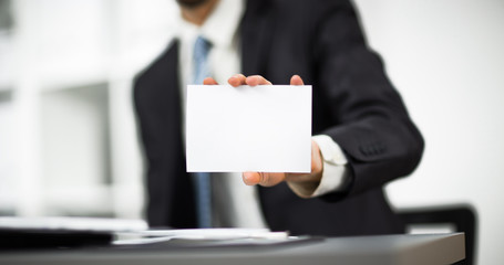 Man's hand showing business card